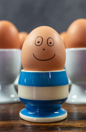 Happy emotion concept one individual boiled egg smiling in different blue striped egg cup surrounded by eggs in white egg cups on a wooden table Banque d'images - 114804862