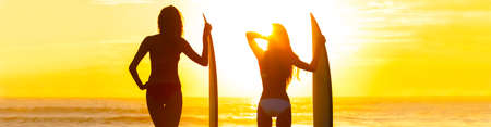 Panoramic web banner rear view silhouettes of beautiful sexy young women surfer girls in bikinis with surfboards on a beach at sunset or sunrise Banque d'images - 114804864