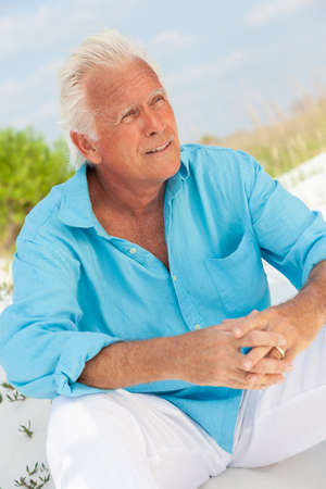 Portrait of a happy attractive handsome senior man sitting down outside on a beach looking thoughtful Banque d'images - 115884146