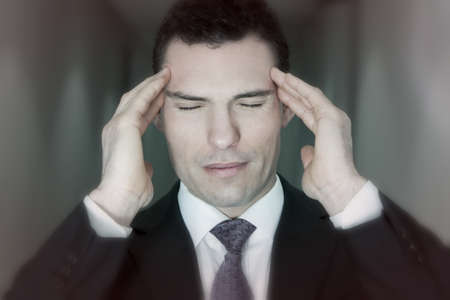 Stressed depressed businessman holding his head in pain from stressful migraine headache Stock Photo