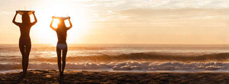 Beautiful young women surfer girls in bikinis with surfboards on a beach at sunset or sunrise panoramic web banner