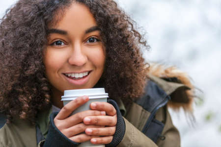 Beautiful happy mixed race African American girl teenager female young woman smiling drinking takeaway coffee outside Banque d'images - 115884168