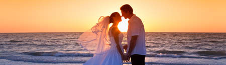 Married couple, bride and groom, kissing at sunset at a beautiful tropical beach wedding panoramic web banner Banque d'images - 115884189