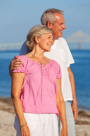 Happy senior man and woman couple standing embracing on vacation on a deserted white sand beach with bright clear blue sky and calm sea Banque d'images - 115884204