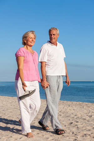 Happy senior man and woman couple walking smiling holding hands on vacation on a deserted tropical beach with bright clear blue sky and calm sea Banque d'images - 115884206