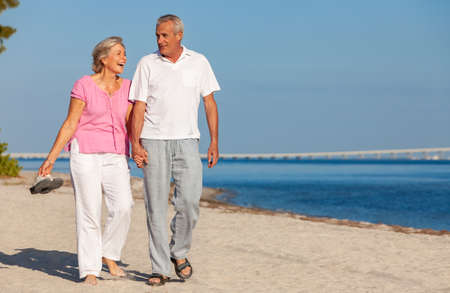 Happy senior man and woman couple walking laughing holding hands on vacation on a deserted tropical beach with bright clear blue sky and calm sea