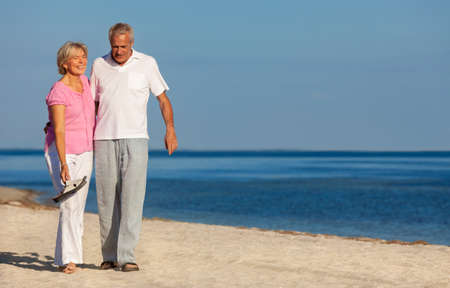 Happy senior man and woman couple walking laughing on vacation on a deserted tropical beach with bright clear blue sky and calm sea Banque d'images - 115884210