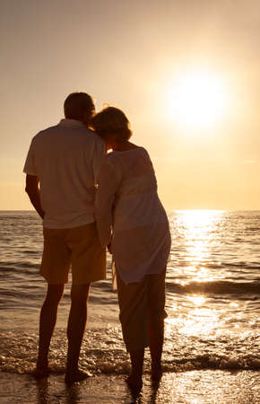 Romantic senior man and woman couple holding hands embracing at sunset or sunrise on a deserted tropical beach Banque d'images - 115884216