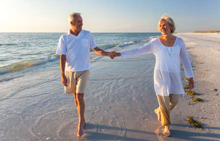 Happy senior man and woman couple walking and holding hands on a deserted tropical beach with bright clear blue sky Stock Photo
