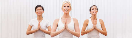Panorama web banner interracial group of three beautiful young women hands in prayer practising yoga position at a gym Banque d'images - 115884219