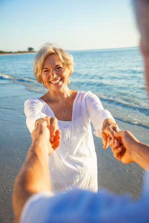 Happy senior man and woman couple dancing and holding hands on a deserted tropical beach at sunset with bright clear blue sky Stock Photo