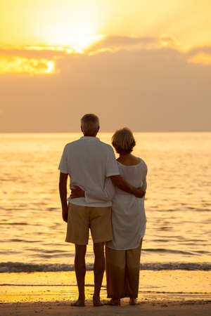 Senior man and woman couple embracing at sunset or sunrise on a deserted tropical beach Banque d'images - 116057363