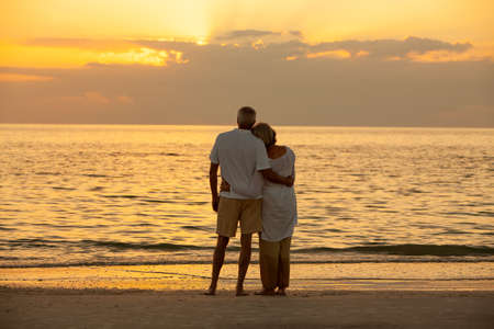 Senior man and woman couple embracing at sunset or sunrise on a deserted tropical beach Banque d'images - 116057364