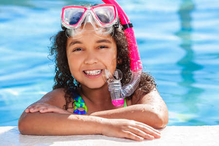 Biracial African American happy young girl child relaxing on the side of a swimming pool wearing pink goggles and snorkel
