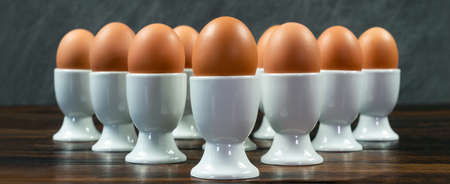 Panoramic web banner ten eggs in white egg cups on a wooden table in a triangle arrangement Banque d'images - 116082177