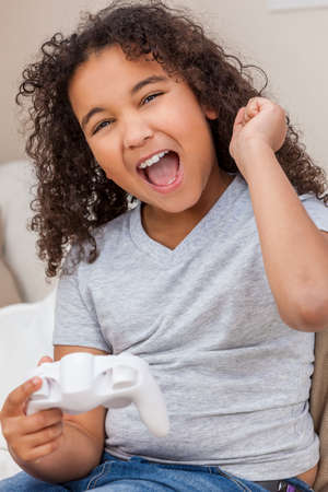 Biracial African American girl, mixed race female child, celebrating winning playing video console games with a white controller Banque d'images - 116057367
