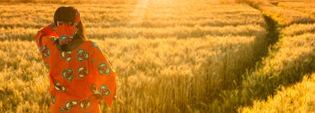 Panoramic web banner African woman in traditional clothes standing, looking to the sun, hand to eyes, in field of barley or wheat crops at sunset or sunrise