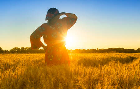 African woman in traditional clothes standing, looking, hand to eyes, in field of barley or wheat crops at sunset or sunrise Banque d'images - 116057374