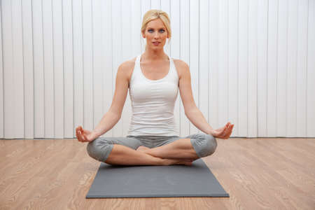 Beautiful woman young female practicing cross legged seated yoga postion indoors at a gym or health spa