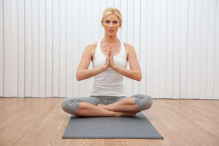 Beautiful woman young female hands in prayer practicing cross legged seated yoga postion indoors at a gym or health spa
