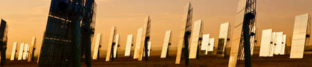 Panoramic web banner field of solar mirror panels harnessing the suns rays to provide alternative green energy at sunrise or sunset