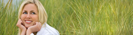 Panoramic web banner blonde girl young woman wearing a white towelling robe sitting in tall natural green grass Banque d'images - 116596375