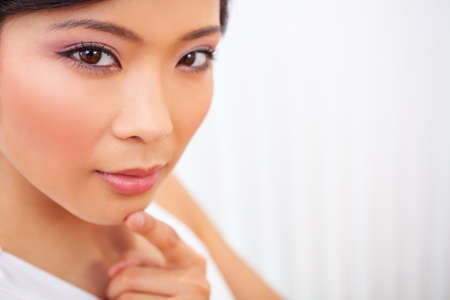 Close up portrait of a beautiful thoughtful Chinese Asian young woman or girl finger on chin thinking Stock Photo