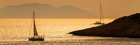 Panoramic web banner silhouettes of yacts or boats sailing at sunset, Hvar, Croatia, Europe