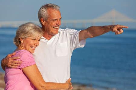 Feliz pareja senior hombre y mujer caminando y abrazándose en una playa tropical desierta con cielo azul claro brillante, el hombre apuntando hacia el horizonte