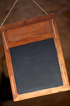 Traditional clean plain or blank wooden blackboard or chalkboard menu sign hanging in a restaurant Banque d'images - 120208111