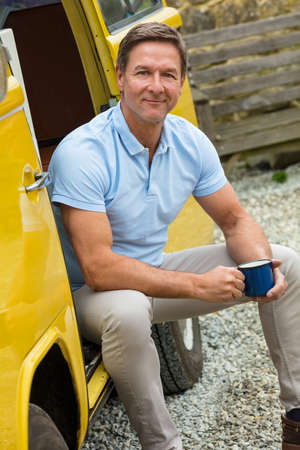 Portrait shot of an attractive, successful and happy middle aged man male wearing a blue polo shirt, sitting in the doorway of a van or truck drinking tea or coffee from a tin cup Banque d'images - 120208112