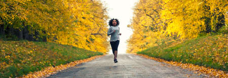 Panoramic web banner beautiful mixed race African American young woman girl teenager fitness running jogging in Autumn Fall trees