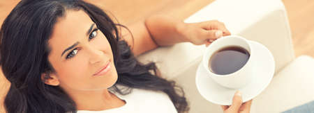 Panoramic web banner beautiful young Latina Hispanic woman or girl with a wonderful enigmatic smile drinking tea or coffee from a white cup at home on her sofa Banque d'images - 120208116