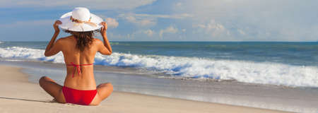 Pnoramic web banner rear view of beautiful young woman in red bikini and a white sun hat sitting on a deserted tropical beach with blue sky, healthy body care sun screen vacation concept