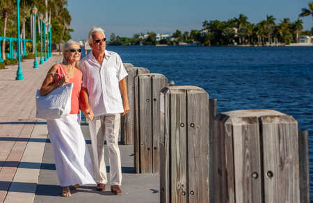 Happy senior man and woman romantic couple together looking out to tropical sea or river with bright clear blue sky
