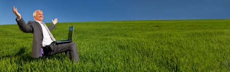 Panoramic web banner green environmental pension business concept of male businessman celebrating using a laptop computer in a green field with a blue sky. Panorama shot on location with copy space.