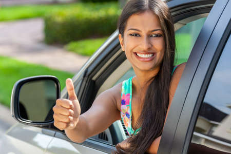 Beautiful Indian Asian young woman or girl leaning out of a car giving a thumbs up in summer sunshine smiling with perfect teeth and long hair. Car hire, driving test concept.