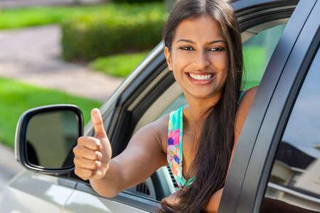 Schöne indische asiatische junge Frau oder ein Mädchen, das sich aus einem Auto lehnt und im Sommersonnenschein einen Daumen hochgibt und mit perfekten Zähnen und langen Haaren lächelt. Autovermietung, Fahrtestkonzept.