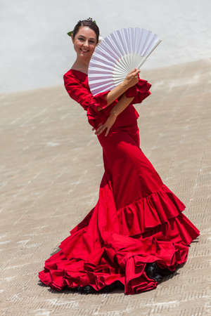 Spanish female woman Flamenco dancer performing outside wearing a red dress posing with a white fan