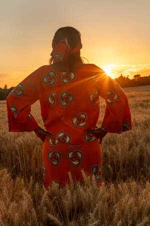 African woman in traditional clothes standing, looking, hands on hips, in field of barley or wheat crops at sunset or sunrise
