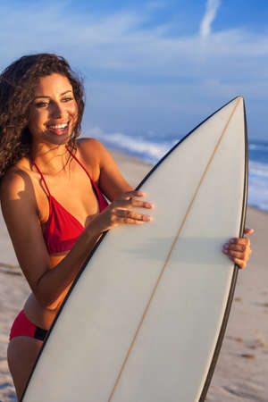 Beautiful young woman surfer girl in red bikini with surfboard standing smiling looking at the surf on a beach with blue sky Imagens