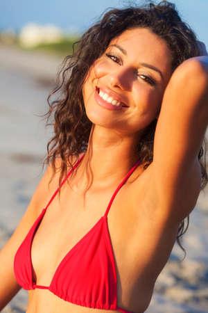 Hermosa joven mujer hispana de raza mixta riendo en bikini rojo en una playa tropical desierta Foto de archivo