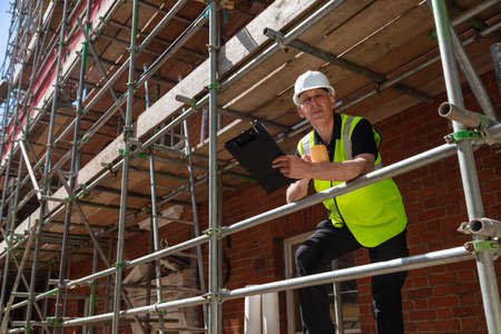 Male builder foreman, construction worker, surveyor or architect on site holding a clipboard and drinking a mug of coffee or tea Stockfoto