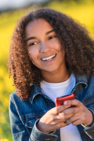 Outdoor portrait of beautiful happy mixed race African American girl teenager female young woman smiling with perfect teeth sending text messaging or using social media on a red mobile cell phone outdoors in yellow flowers