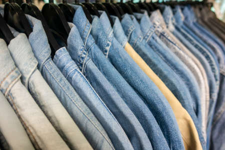 Male mens denim jeans shirts sorted on clothes hangers on a shop wardrobe closet rail