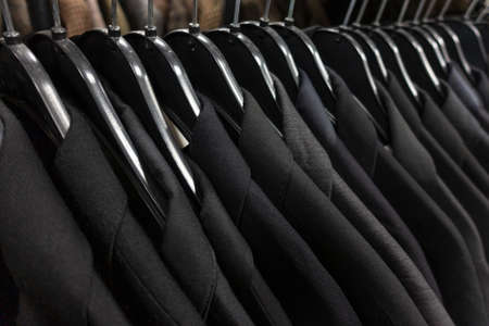 Male mens black, gray and blue dark business suits on hangers on a shop, wardrobe or closet rail