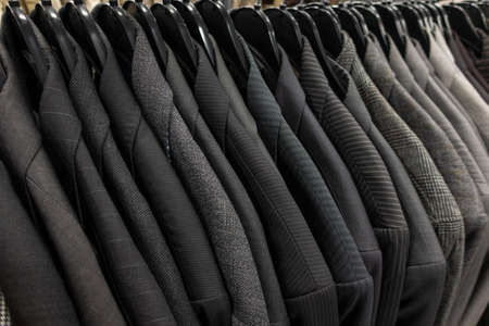 Male mens gray business suits on hangers on a shop, wardrobe or closet rail Stockfoto - 130776569