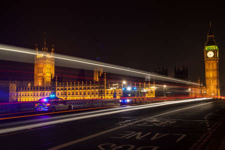 Police, ambulance emergency vehicles at night on Westminster Bridge by Big Ben, Houses of Parliament, London, England