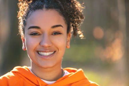 Outdoor portrait of beautiful happy mixed race African American girl teenager female young woman smiling with perfect teeth in golden evening sunshine