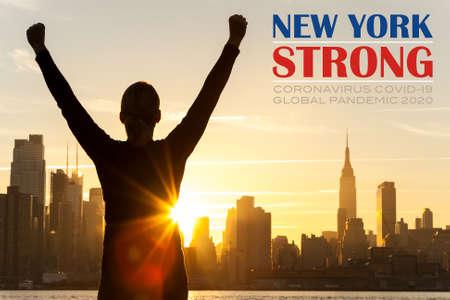 Silhouette einer erfolgreichen Frau oder eines Mädchens, die bei Sonnenaufgang oder Sonnenuntergang vor der Skyline von New York City mit New York Strong Coronavirus COVID-19 Global Pandemic 2020 Text feiert Standard-Bild